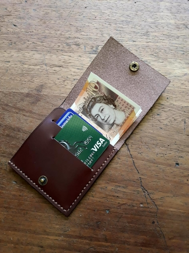 Hand made leather wallet open with cards & money