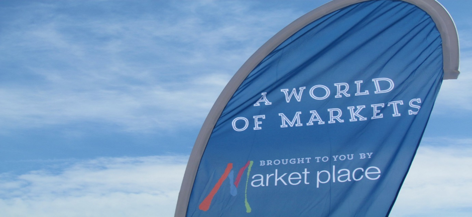 World of Markets banner flag against a blue sky with white clouds